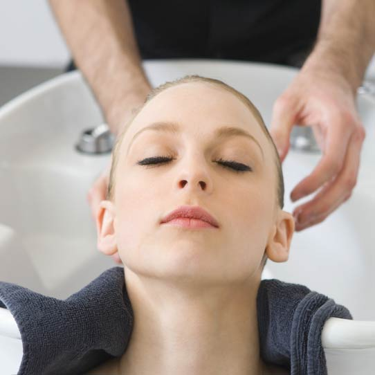 Dame vasker håret hos frisøren